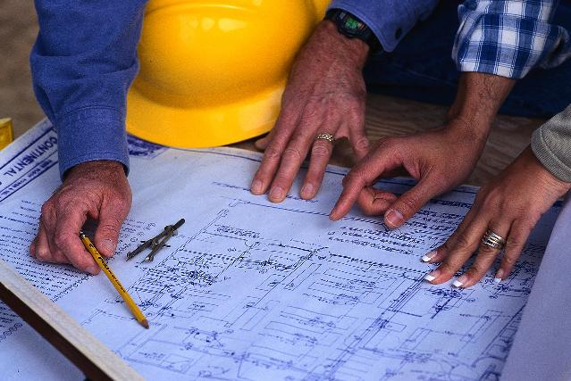 Hands of Couple Looking at Blueprints